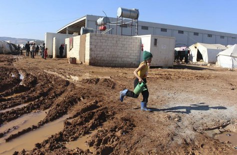 A Syrian refugee girl carries a watering can as she walks on mud at the Bab Al-Salam refugee camp in Azaz, near the Syrian-Turkish border Fe