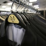 Suits hang on a rack at a Men's Wearhouse store in Pasadena, California June 25, 2013. REUTERS/Mario Anzuoni