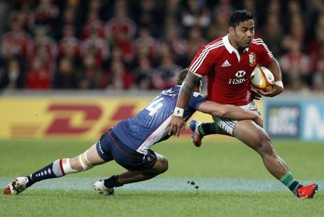 British and Irish Lions player Manu Tuilagi (R) is tackled by Tom English from the Melbourne Rebels during their rugby game in Melbourne Jun