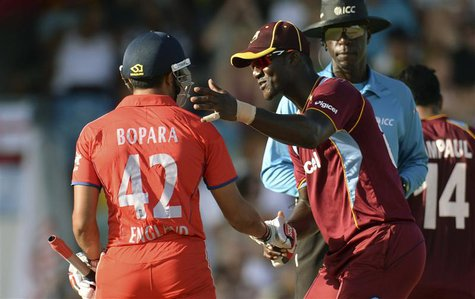 West Indies' Darren Sammy shakes hands with England's Ravi Bopara (L) during the first T20 international cricket match at Kensington Oval in
