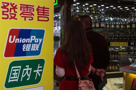 Chinese visitors walk past a sign for China UnionPay outside a pawnshop in Macau, in this picture taken November 20, 2013. REUTERS/Tyrone Si
