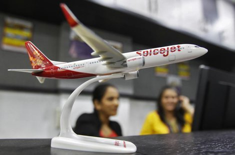 Employees work inside a travel agency office besides a model of a SpiceJet aircraft in the western Indian city of Ahmedabad February 14, 201