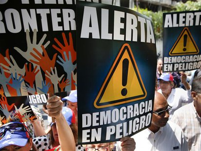 Anti-government protesters hold placards during a gathering against Nicolas Maduro's government outside the Embassy of Portugal in Caracas M