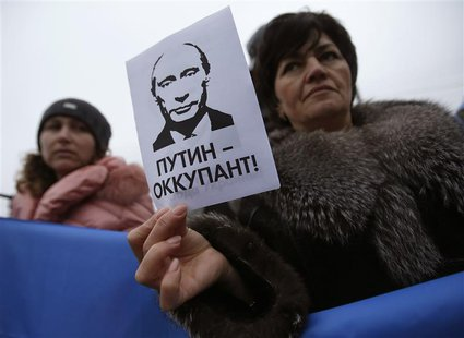 "A woman holds a sign with a portrait of Russian President Vladimir Putin and the words ""Putin - Occupant"" during a pro-Ukrainian rally in Si"