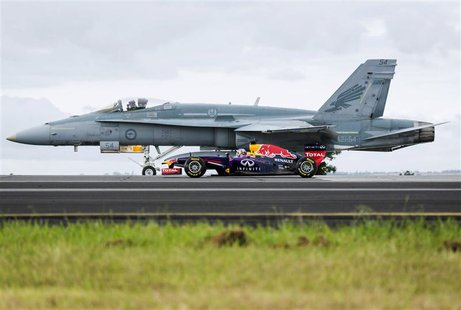 Formula One driver Daniel Ricciardo of Australia drives his Infiniti Red Bull car alongside a Royal Australian Air Force F/A-18 Hornet plane