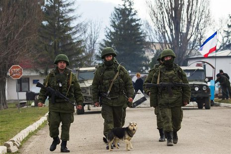 Armed men, believed to be Russian servicemen, march outside an Ukrainian military base in the village of Perevalnoye near the Crimean city o
