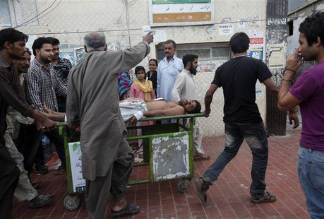 Rescue workers and relatives wheel an injured man on a stretcher, who was attacked by unknown gunmen, at Civil Hospital in Karachi March 12,