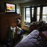 A young child watches television in an NYCHA apartment after receiving electricity just minutes before for the first time following Hurrican
