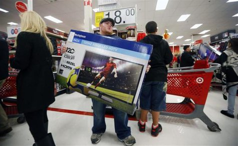 A holiday shopper carries a discounted television to the checkout at the Target retail store in Chicago, Illinois, in this file photo taken