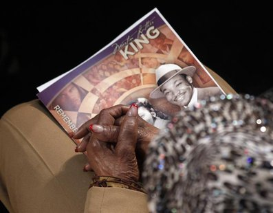 A visitor holds a commemorative booklet as she listens during the Martin Luther King, Jr. 46th Annual Commemorative Service at Ebenezer Bapt