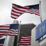 Flags wave behind a General Motors Corp sign in downtown in Detroit May 28, 2009. REUTERS/Mark Blinch
