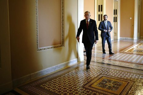 U.S. Senate Majority Leader Harry Reid (D-NV) (C) walks to address reporters after the weekly Republican caucus luncheon at the U.S. Capitol