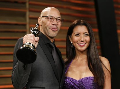 "Writer John Ridley holds up his award for best adapted screenplay for ""12 Years a Slave"" as he arrives with his wife Gayle at the 2014 Vanit"