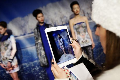 A woman takes a photo of models presenting creations from the Clover Canyon Autumn/Winter 2013 collection during New York Fashion Week, Febr
