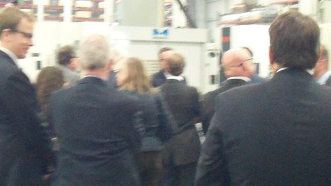 Calley and the other conferees huddle around a plastic injection mold during the tour.