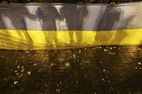 Participants of an anti-war rally hold a national flag as eggs thrown by pro-Russia protesters cover the floor during their clashes in Donet