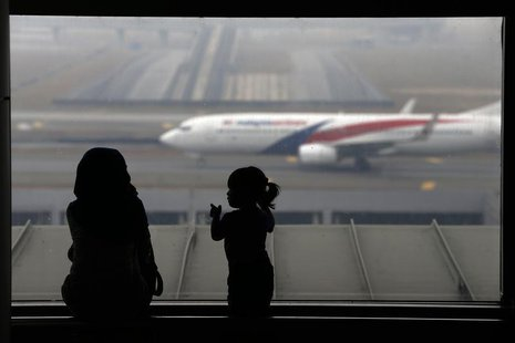 A woman and a girl look at a Malaysia Airlines plane on the tarmac of Kuala Lumpur International Airport March 13, 2014. REUTERS/Damir Sagol