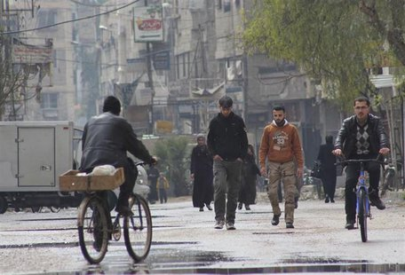 People walk as others ride on a bicycle along a street in Arbeen, in the eastern Damascus suburb of Ghouta, March 9, 2014. Picture taken Mar