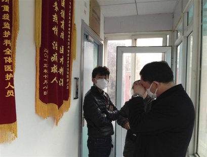 Friends of human right activist Cao Shunli stand in front of an intensive care unit where Cao is hospitalized as they are not allowed to go