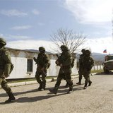 Armed men, believed to be Russian servicemen, walk outside a Ukrainian military base in Perevalnoye, near the Crimean city of Simferopol, Ma