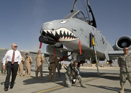 "US Secretary of Defense Robert Gates (L) greets the crew and looks over an A-10 ""Warthog"", a close support aircraft, during an unannounced v"