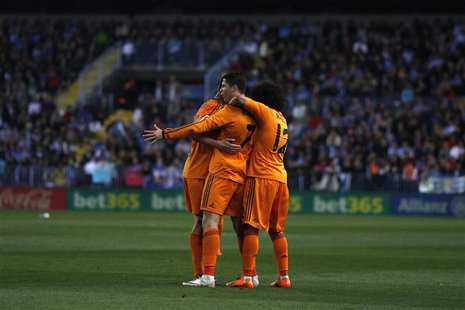 Real Madrid's Cristiano Ronaldo (C) is congratulated by his teammates after scoring a goal against Malaga during their Spanish First Divisio