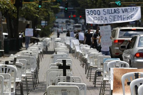Anti-government protesters placed black crosses on white chairs, representing victims who died from violence, during a demonstration in Cara