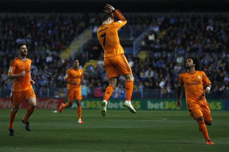 Real Madrid's Cristiano Ronaldo (C) celebrates after scoring a goal against Malaga during their Spanish First Division soccer match at La Ro