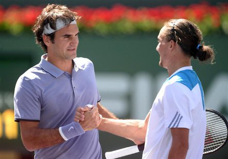 Mar 15, 2014; Indian Wells, CA, USA; Roger Federer (SUI), left, shakes hands with Alexandr Dolgopolov (UKR) after their semifinal match at t