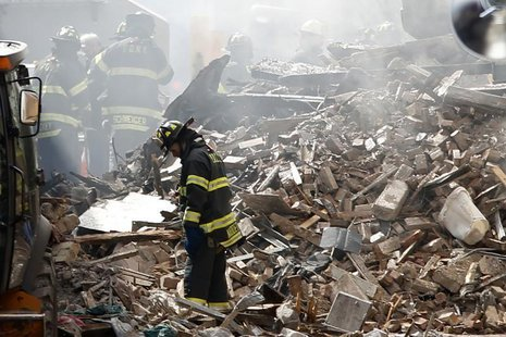 New York City emergency responders search through the rubble at the site of a building explosion in the Harlem section of New York, March 13