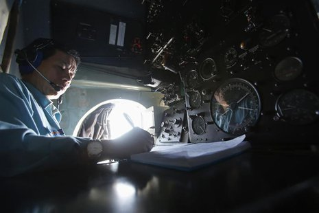Senior Lieutenant Phung Truong Son takes notes while working within the cockpit of a Vietnam Air Force AN-26 aircraft during a mission to fi