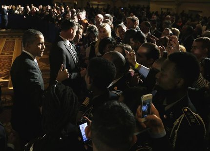 U.S. President Barack Obama (L) gives a thumbs-up to supporters after addressing the winter meeting of the Democratic National Committee in