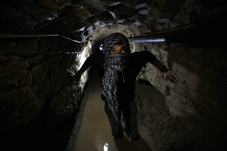 A Palestinian works inside a smuggling tunnel flooded by Egyptian forces, beneath the Egyptian-Gaza border in Rafah, in the southern Gaza St
