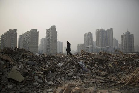 A man walks in an area where old residential buildings are being demolished to make room for new skyscrapers in central Shanghai January 20,
