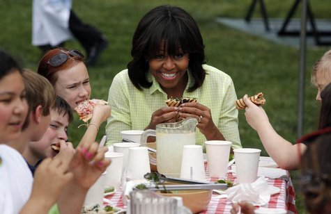 U.S. first lady Michelle Obama eats with school kids after they harvested vegetables from the summer crop from inside the White House Kitche