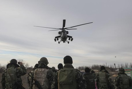 A Russian army MI-35 military helicopter patrols the area as Ukrainian servicemen guard a checkpoint near the village of Strelkovo in Kherso
