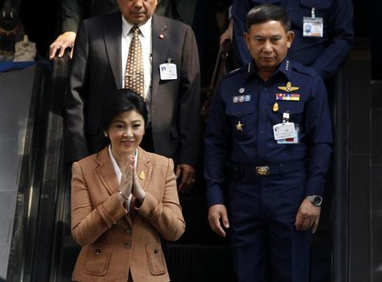 Thailand's Prime Minister Yingluck Shinawatra gestures as she leaves the Royal Thai Air Force Headquarters, after a defense meeting in Bangk