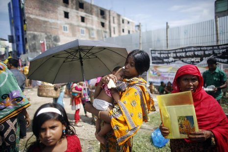 A garment worker who survived the Rana Plaza building collapse, carries her child during a protest to demand for compensation, on the six mo