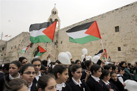 Palestinian girls hold flags and balloons in front of the Church of Nativity during a rally in the West Bank town of Bethlehem March 17, 201