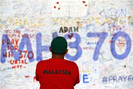 A man stands in front of a board with messages of hope and support for the passengers of the missing Malaysia Airlines MH370 at the departur