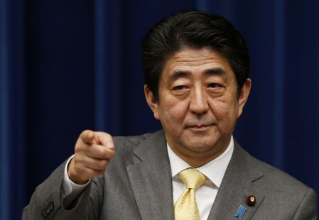 Japan's Prime Minister Shinzo Abe points to a reporter during a news conference at his official residence in Tokyo March 10, 2014, a day bef