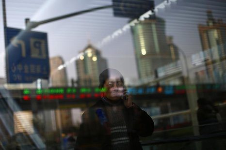 A man walks out of a subway station as he talk on the phone at the financial district of Pudong in Shanghai March 11, 2014. REUTERS/Carlos B