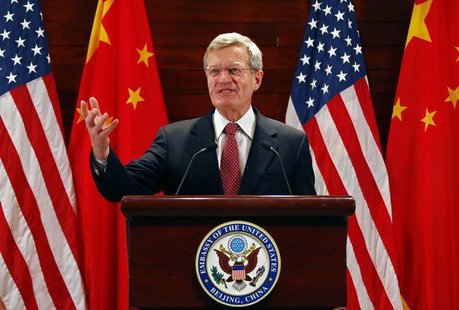 U.S. Ambassador to China Max Baucus gestures in front of Chinese and American national flags during a news conference at the U.S. Embassy, u
