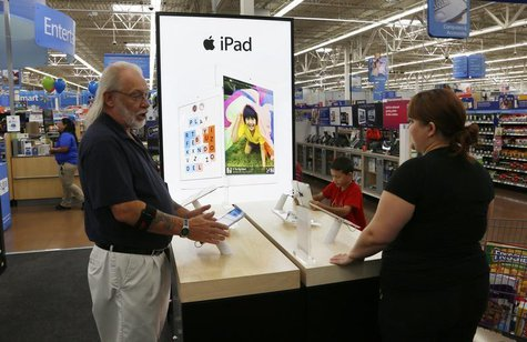 A Walmart employee (L) explains Apple iPad options to a customer at a Walmart Supercenter in Rogers, Arkansas June 6, 2013. REUTERS/Rick Wil