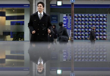 Pedestrians pass by an electronic board displaying stock prices, which are reflected in a polished stone surface, in Tokyo March 7, 2014. RE