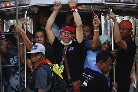 Anti-government protesters travel on a pick-up truck near the Interior Ministry building, which is being surrounded by fellow protesters, in