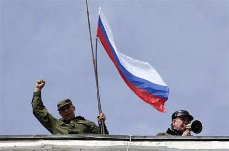 A man holds a Russian flag on the roof of the naval headquarters in Sevastopol, March 19, 2014. REUTERS/Vasily Fedosenko