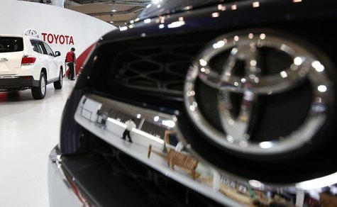 A showroom staff member works under the logo of Toyota Motor Corp, between cars displayed at its showroom in Tokyo February 4, 2014. REUTERS