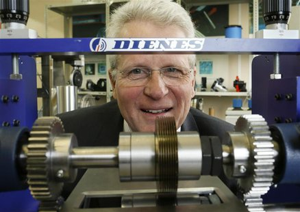Bernd Supe-Dienes, director of the 1913 founded German industrial knife manufacturer Dienes poses for a picture behind an industrial knife m
