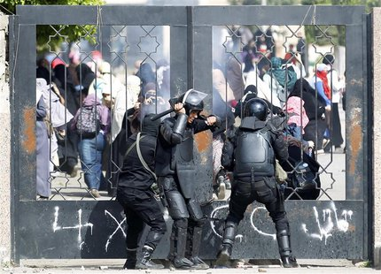 Riot police attempt to break open the entrance of the al-Azhar University Campus during clashes with female university students, who are sup